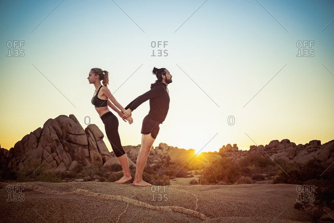 Hispanic couple stretching arms in desert standing back to back