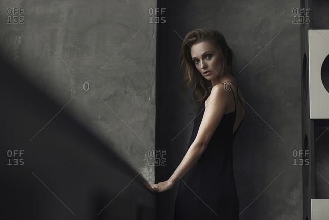 Serious Caucasian woman standing near wall