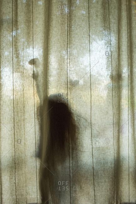 Silhouette of Caucasian girl touching heart-shape behind window curtain