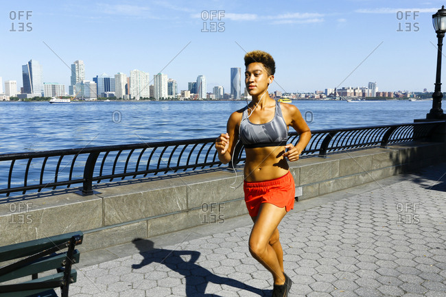 Mixed race woman running at waterfront listening to ear buds