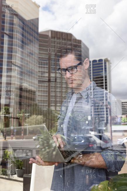 Caucasian man typing on laptop near window in city