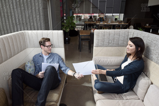 Caucasian couple on sofas using laptop and reading paperwork