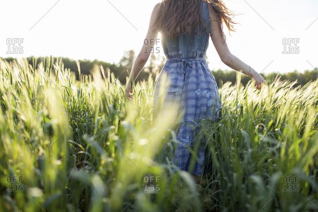 Caucasian woman walking in field of tall grass