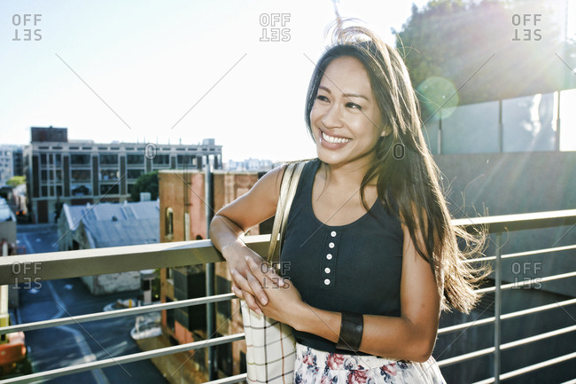 Smiling Asian woman leaning on rooftop