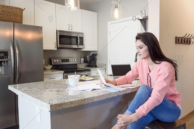 Caucasian woman reading paperwork in kitchen