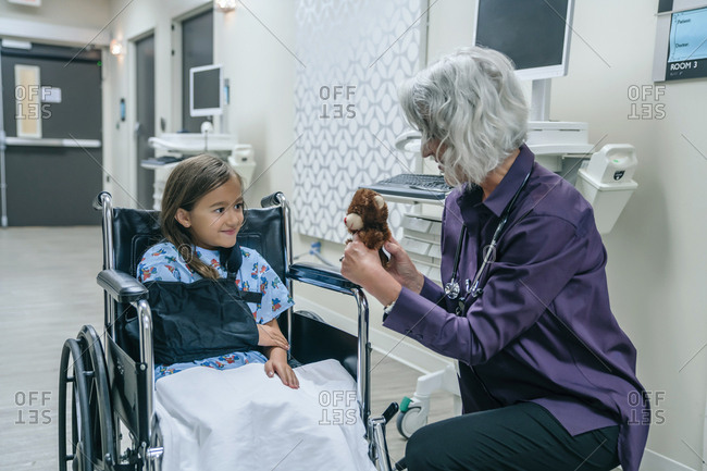 Doctor showing teddy bear to girl in wheelchair