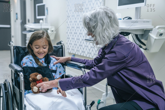 Doctor giving teddy bear to girl in wheelchair
