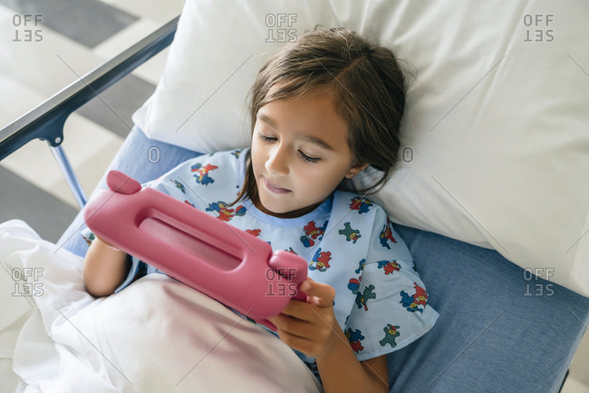 Mixed race girl using digital tablet in hospital bed