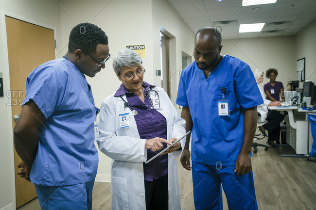 Doctor and nurses discussing digital tablet