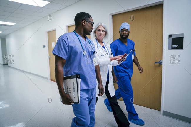 Doctor and nurses discussing digital tablet in hospital
