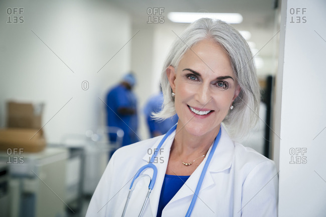 Portrait of Caucasian doctor leaning on wall in hospital