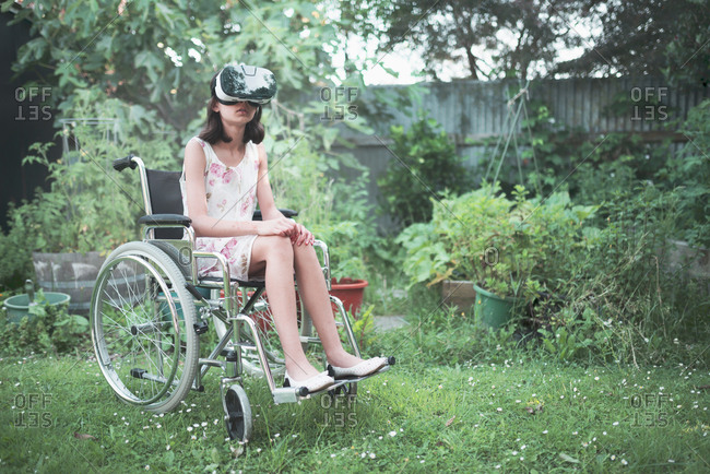 Mixed race girl in wheelchair using virtual reality goggles in backyard