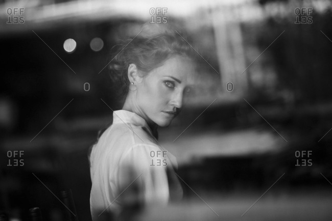 Portrait of serious Caucasian woman behind window