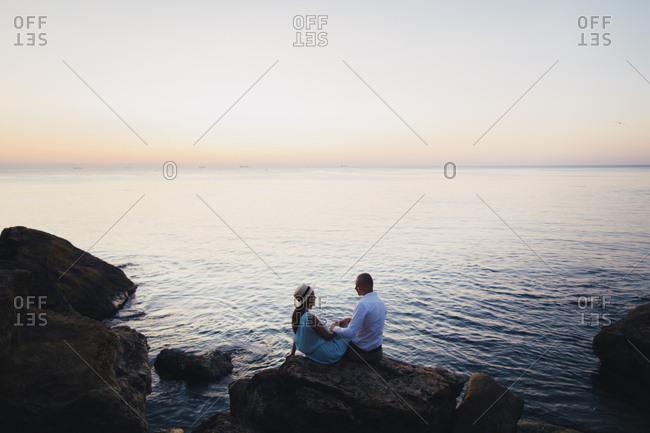 Caucasian couple sitting on rock near ocean at sunset