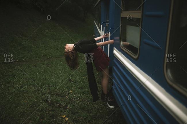 Caucasian woman hanging on train