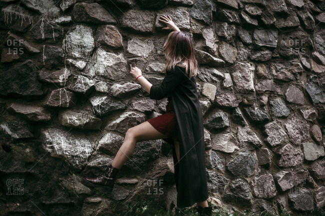 Caucasian woman climbing rock wall