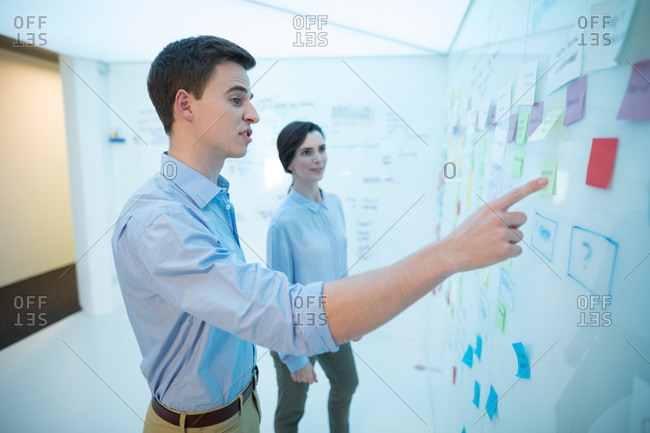 Male and female executives reading sticky note in futuristic office