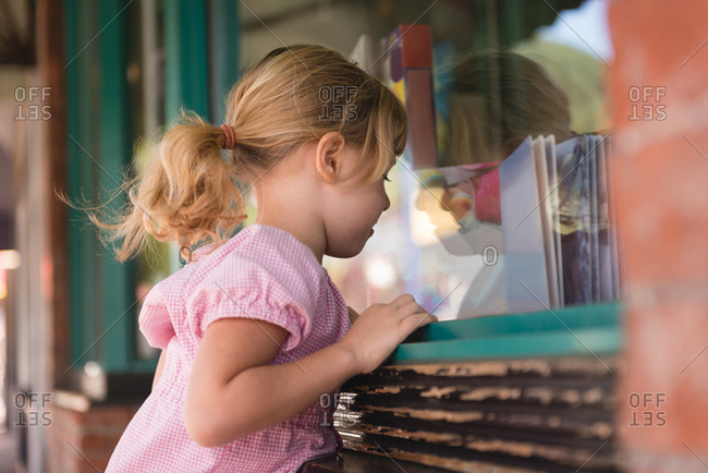 Girl peeping through the glass window outside the book store