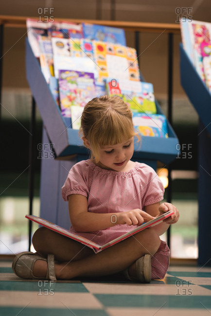 Cute girl reading book in store