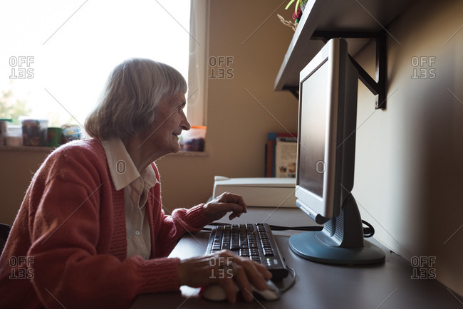 Senior woman working on computer at nursing home