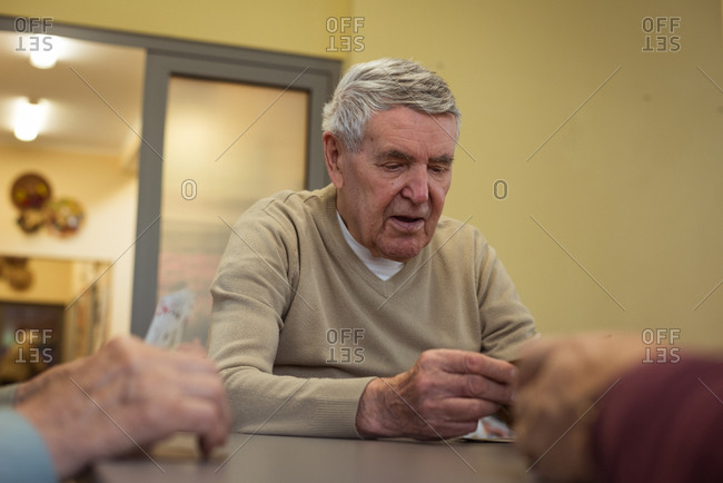 Senior man playing cards at nursing home