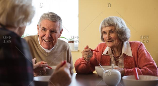Smiling senior friends interacting while having breakfast at nursing home