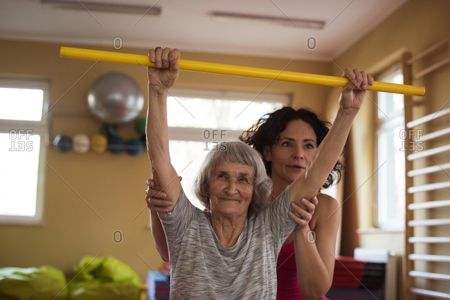 Female therapist assisting senior woman with exercise stick in nursing home