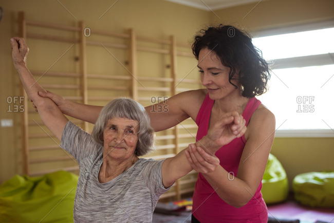 Female therapist assisting senior woman with hand exercise at nursing home