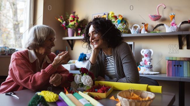 Smiling senior woman interacting with caretaker at nursing home