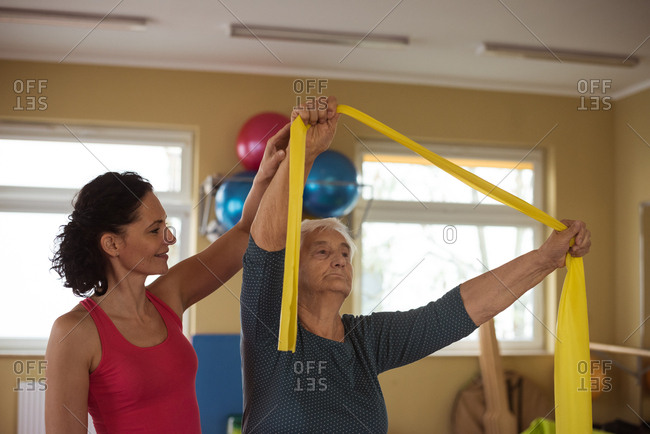 Female therapist assisting senior woman with exercise band in nursing home