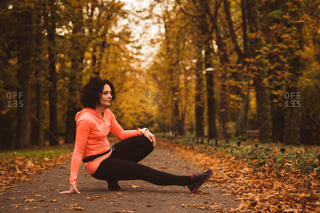 Woman performing stretching exercise in forest during autumn season