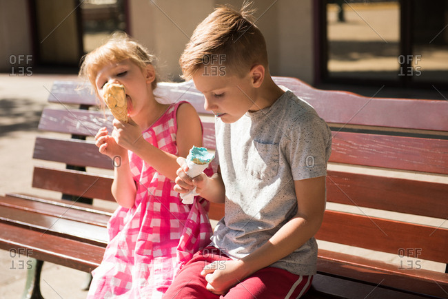 Sibling eating ice cream on bench during sunny day