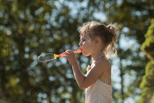 Cute girl playing with bubble wand in park