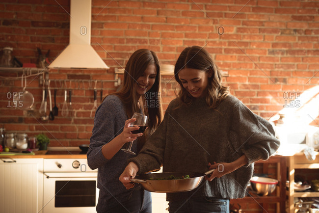 friends having wine while preparing food in kitchen