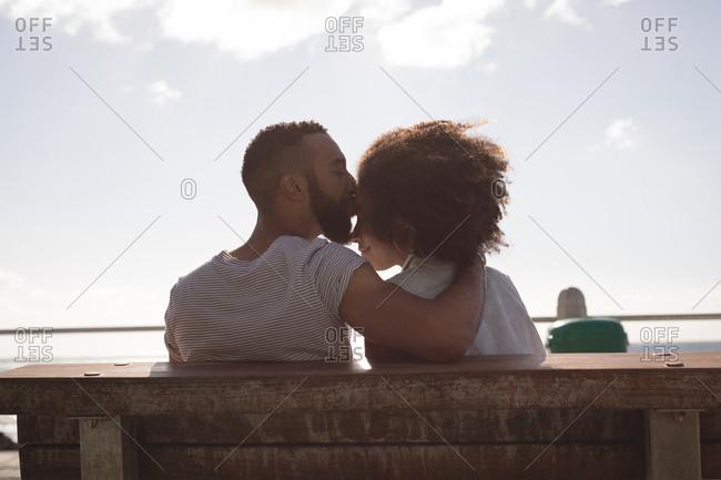 Man kissing woman on forehead near sidewalk