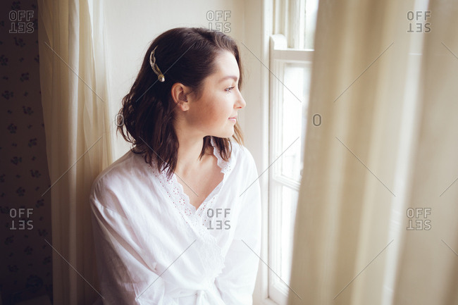 Beautiful woman looking out of the window on a sunny day