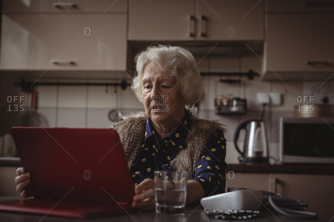 Senior woman using digital tablet in the kitchen at home