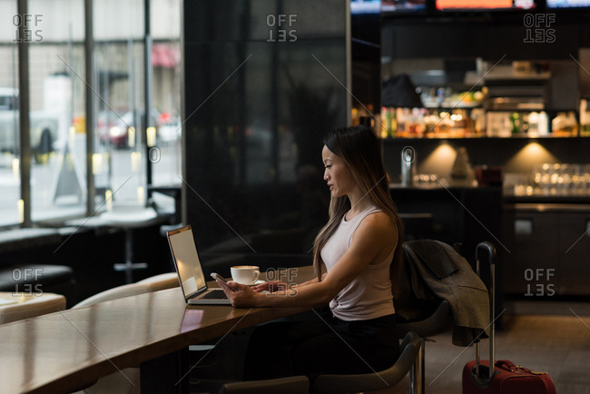 Businesswoman holding mobile phone while working on laptop in the cafeteria