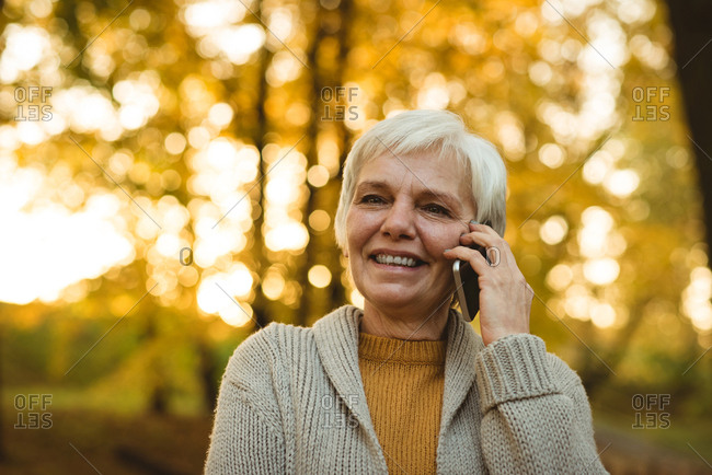 Close-up of smiling senior woman talking on phone in autumn park