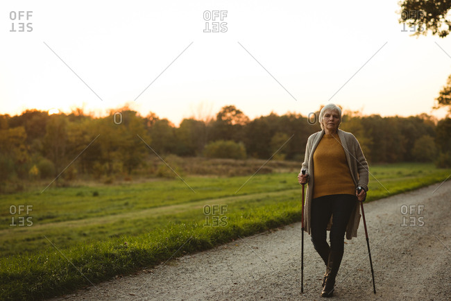 Senior woman walking on a dusty road with walking sticks at the time of dawn