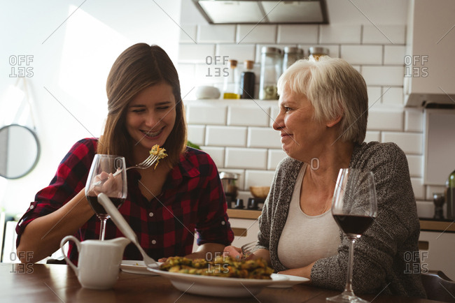 Senior woman and daughter eating omelet and wine for breakfast