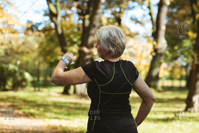 Senior woman using a smart watch in a park on a sunny day
