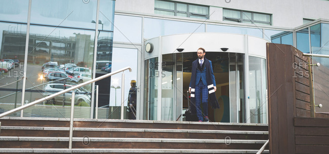 Sophisticated businessman walking out of the hotel