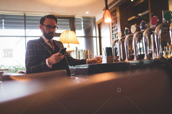 Businessman using mobile phone while having whiskey in bar