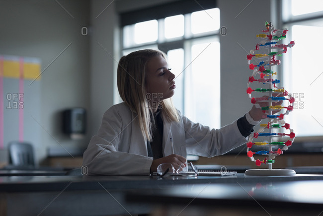 Teenage girl examining the molecule model in laboratory at university