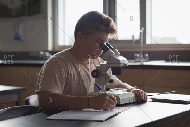 Teenage boy experimenting on microscope in laboratory at university