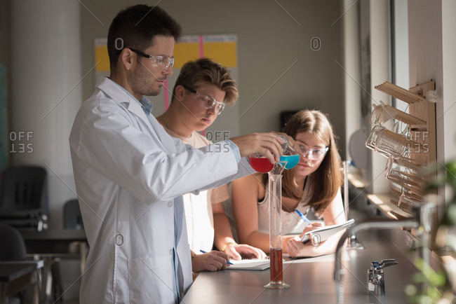 Teacher assisting students in chemical experiment at laboratory