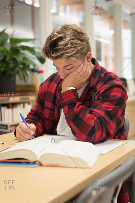 Teenage boy studying in library at university