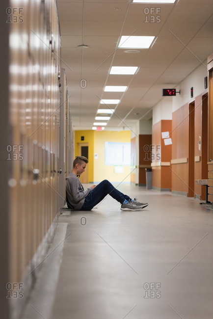 Teenage boy sitting in locker room at university