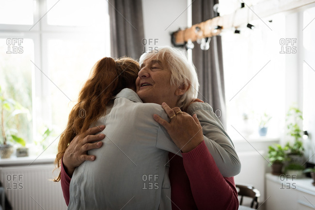 Emotional grand mother and grand daughter embracing each other in living room